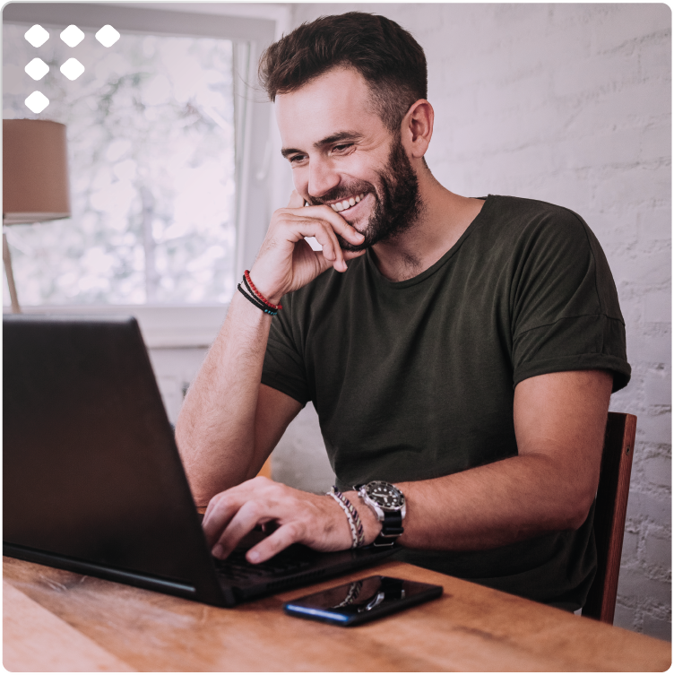 Man looking at laptop and chatbot in mobile app